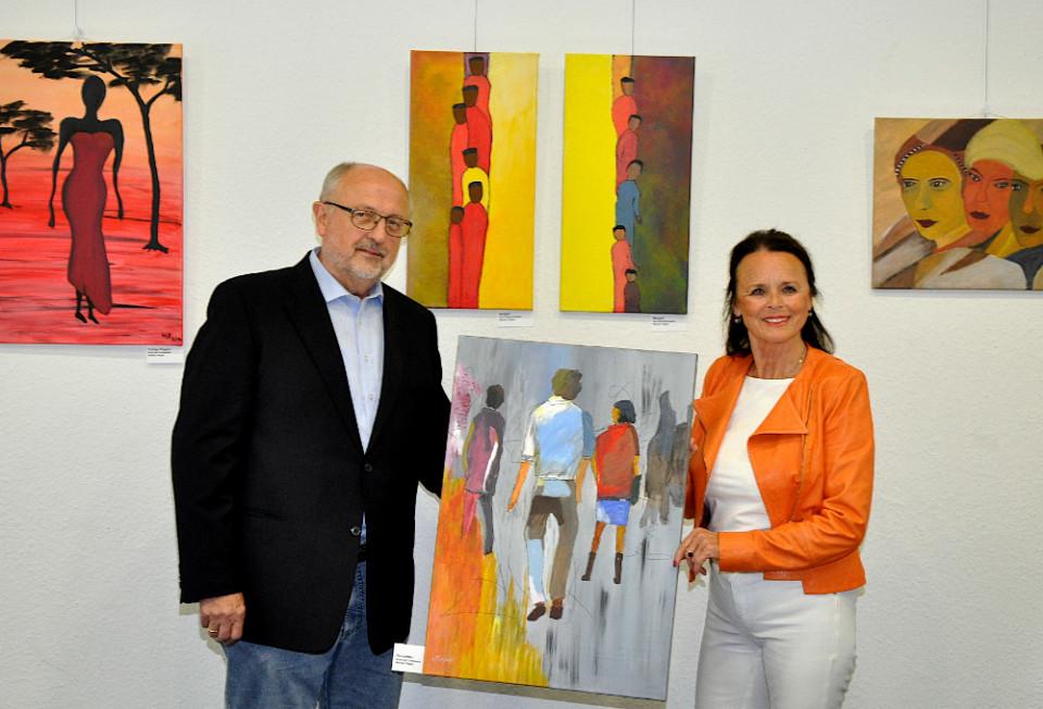 """Werner Pieper und Elke Hardieck (v.l.) in der neuen Ausstellung. Das Werk, das sie in den Händen halten, ist mit """"Passanten"""" betitelt."""