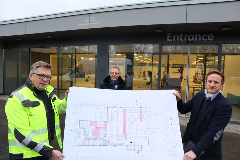 Bernhard Riepe, Krisenstabsleiter Frank Scheffer und Henrik Egeler präsentieren vor dem Eingang den Plan für das Impfzentrum. Foto: Kreis Gütersloh