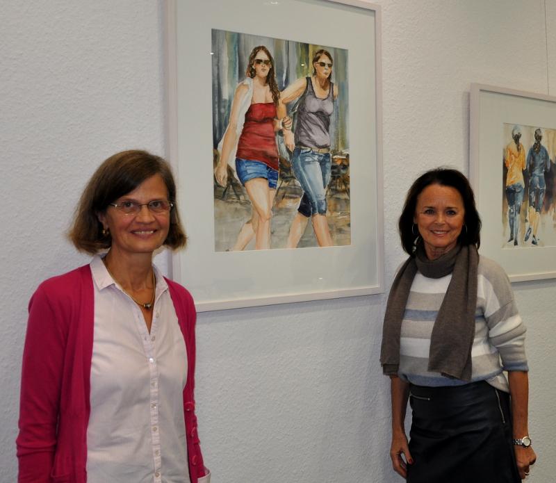 Margret Wenzke (l.) und Elke Hardieck vor einem Aquarell, das eine sommerliche Straßenszene zeigt.