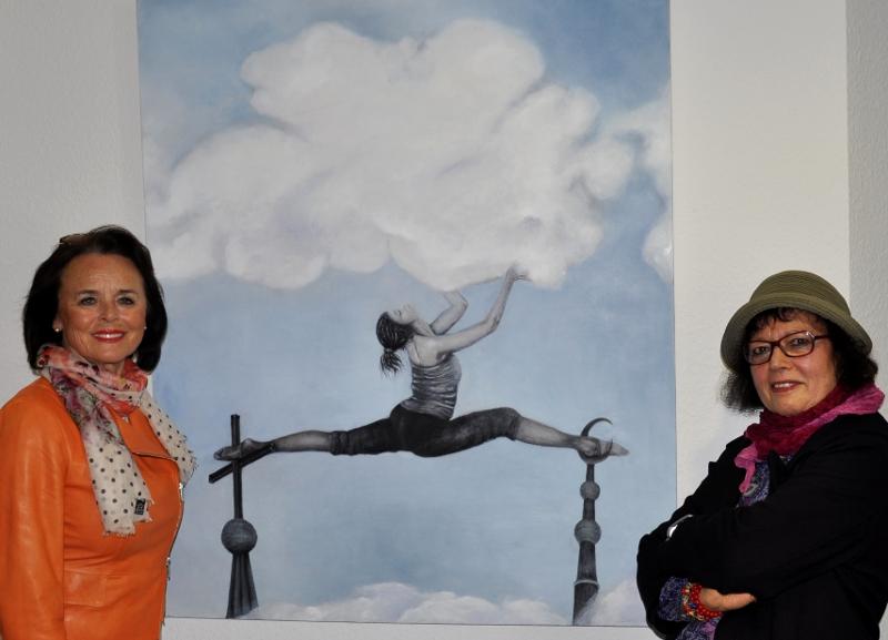 """Elke Hardieck und Serpil Neuhaus (v.l.) vor dem Gemälde """"Spagat zwischen den Kulturen"""", dem das Motto der Ausstellung entnommen ist."""